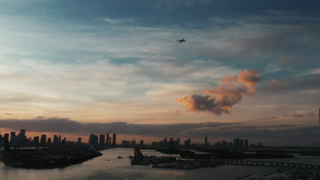 panning shot showing an aircraft flying over miami beach at sunset, florida, united states of america - miami dade county stock videos & royalty-free footage
