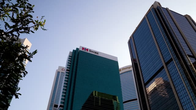 vidéos et rushes de panning shot showing corporate buildings in a downtown district, hong kong - façade