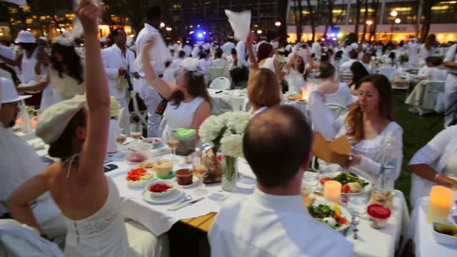 vídeos y material grabado en eventos de stock de panning shot thousands of people all dressed in white set up picnic tables for the diner en blanc event on september 18 2013 in new york city some... - silla plegable