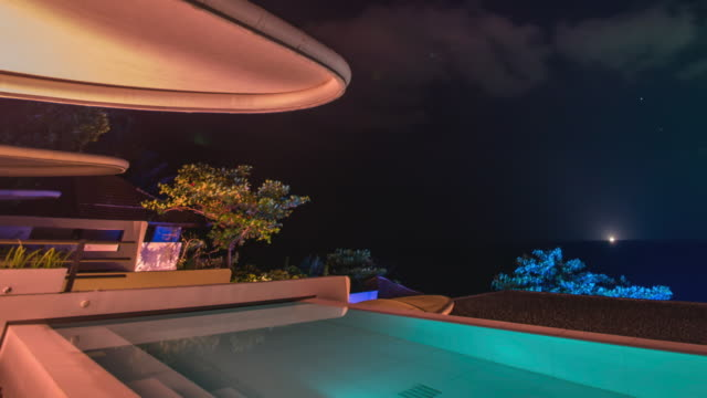 panning shot time-lapse night scenery of illuminating pool villa in thailand - infinity pool stock videos & royalty-free footage