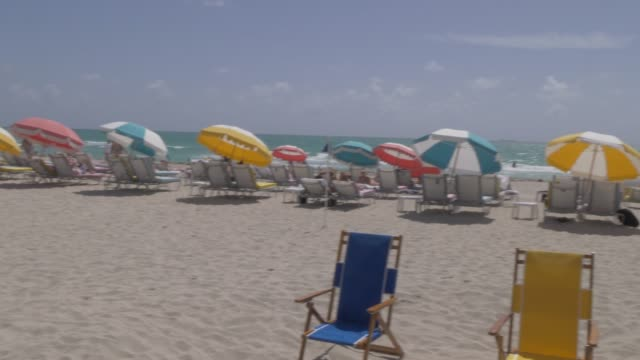 Panning shot to colourful sunshades on Miami Beach, South Beach, Miami, Florida, United States of America, North America