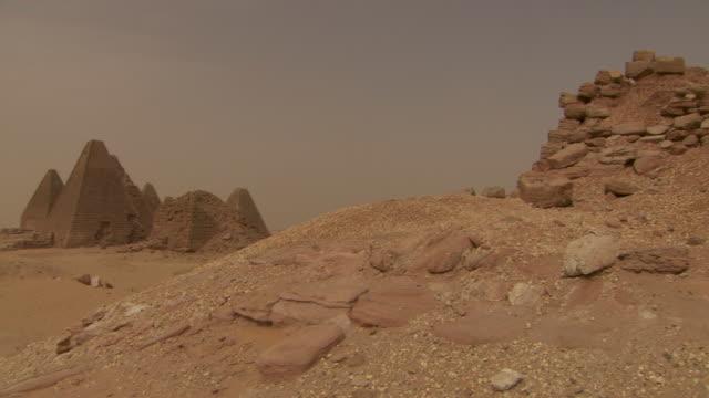 vídeos de stock, filmes e b-roll de panning shot to the ancient pyramid tombs at nuri in sudan.  - sudão