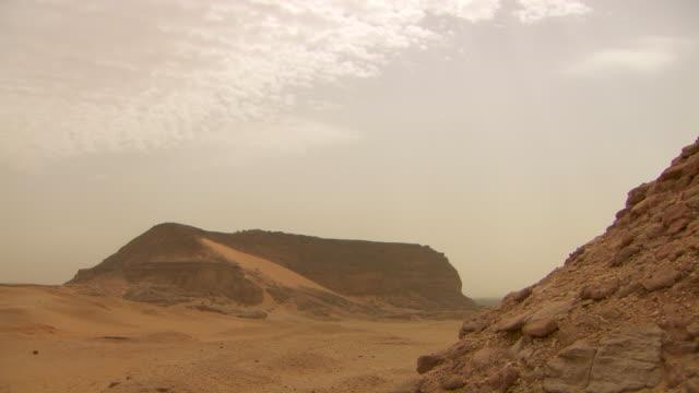 vídeos de stock, filmes e b-roll de panning shot to the sacred mountain of jebel barkal at nuri in sudan. - sudão