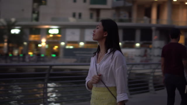 vidéos et rushes de panning shot, woman walks in dubai at dusk - plan en travelling