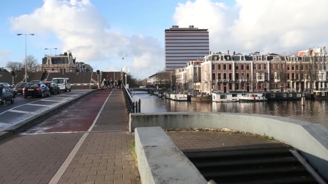 vídeos de stock, filmes e b-roll de panning shots from canal waterway to the offices of the dutch central bank also known as de nederlandsche bank nv on the skyline in amsterdam... - produto interno bruto