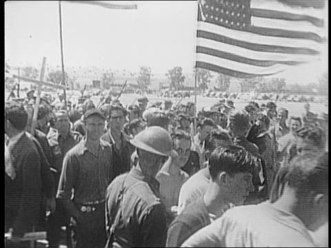 vidéos et rushes de panning shots of military vehicles driving through crowd in front of north american aviation plant / line of soldiers marching through crowd / armed... - 1941