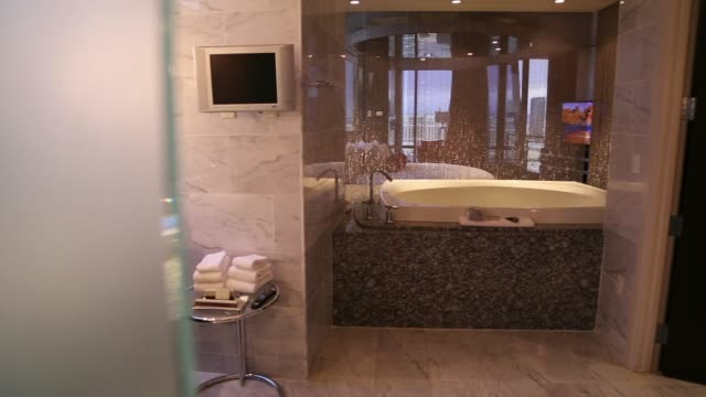 Panning shots of the bedroom and elegant bath tub within a luxury suite at the Palms Hotel Casino in Las Vegas Nevada Closeup shot of the shower...