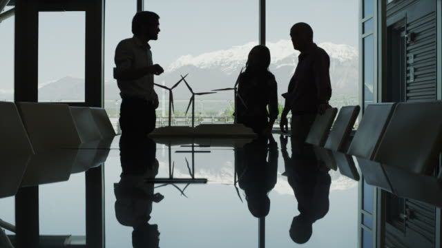 panning silhouette of business people looking at model wind turbines in conference room / provo, utah, united states,  - provo stock videos and b-roll footage