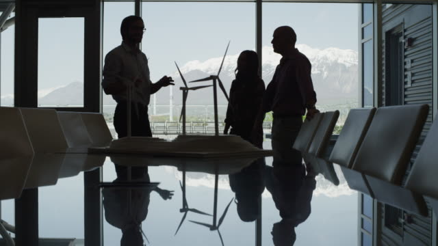 Panning silhouette of business people looking at model wind turbines in conference room then shaking hands / Provo, Utah, United States,