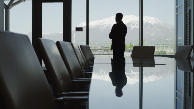 panning silhouette of businessman standing in conference room / provo, utah, united states,  - provo stock videos & royalty-free footage