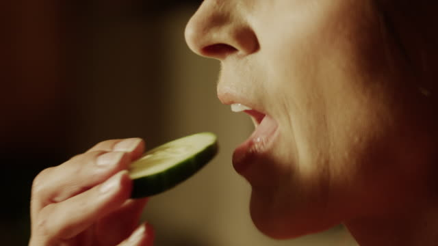 Panning, Slow Motion close up of woman biting into cucumber slice / Cedar Hills, Utah, United States