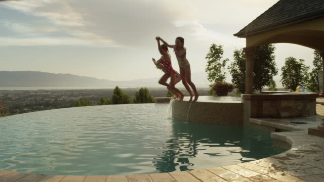 panning slow motion medium shot of girls jumping into infinity pool / cedar hills, utah, united states - infinity pool stock videos & royalty-free footage