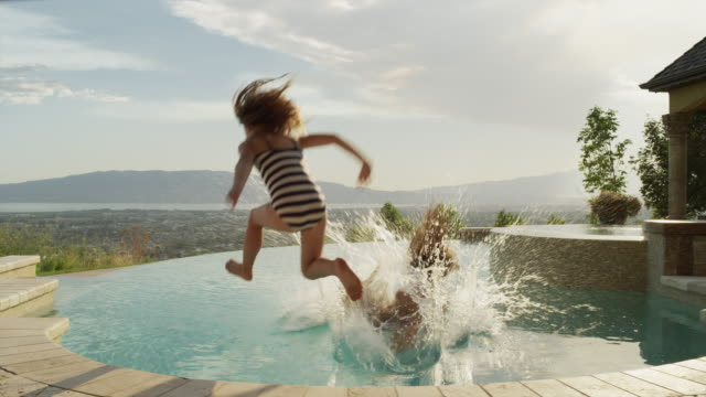 panning slow motion medium shot of girls running and jumping into infinity pool / cedar hills, utah, united states - infinity pool stock videos & royalty-free footage
