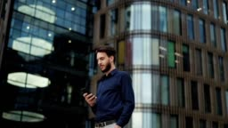 Panning slow motion shot of confident young businessman text messaging on cell phone while standing in city street with hand in pocket and looking away thoughtfully, low angle view