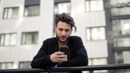 Panning slow motion shot of handsome young man text messaging on cell phone and looking up thoughtfully leaning on railing in street