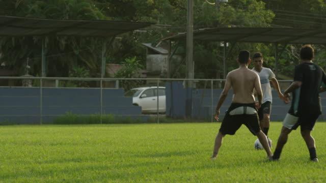 panning slow motion wide shot of soccer teams playing on field / esterillos, puntarenas, costa rica - puntarenas stock-videos und b-roll-filmmaterial