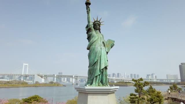 vídeos de stock e filmes b-roll de 4k panning statue of liberty in odaiba with rainbow bridge in tokyo , japan - estátua da liberdade