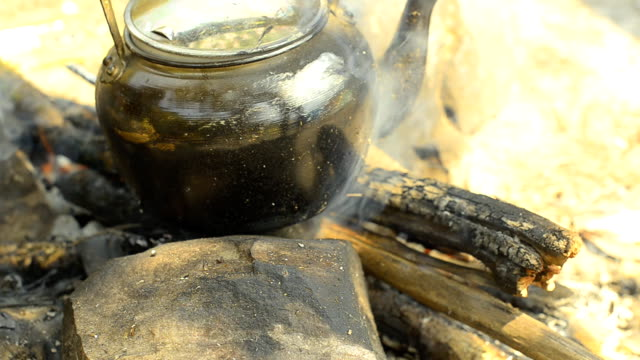 panning: steaming tea kettle  by traditional method and adding wooden fire - tea kettle stock videos & royalty-free footage
