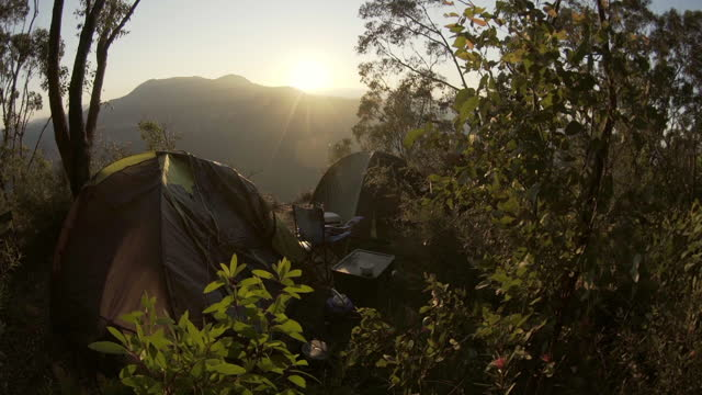 panning: tents amidst plants against sky at sunrise - blue mountains national park, australia - tent stock videos & royalty-free footage