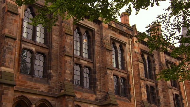 panning the exterior wall of the gothic glasgow university with soaring arched windows, support columns, and a bright gray sky - stone object stock videos & royalty-free footage