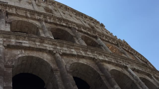 vidéos et rushes de panning the facade of the colosseum towering above, rome - gladiateur