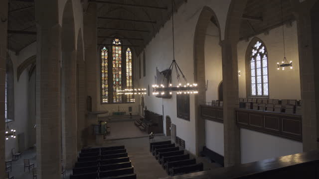 panning the full interior length of an old german church with soaring stained glass windows, pews, vaulted ceiling, and stone carvings - erfurt, germany - apse stock videos & royalty-free footage