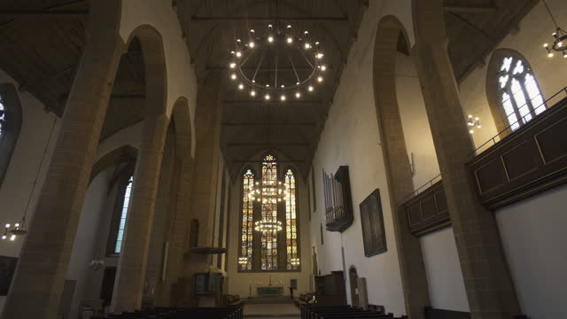 panning the nave of an old german church, with soaring arches, pews, windows, stained glass, high walls, organ pipes, and a distant altar - erfurt, germany - church stock videos & royalty-free footage