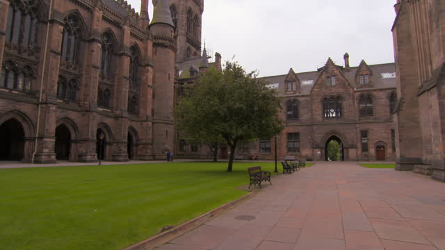 panning the outside courtyard at glasgow university on a bright cloudy day, with soaring gothic arches, windows, towers, green grass, walkways, and people - cathedral stock videos & royalty-free footage