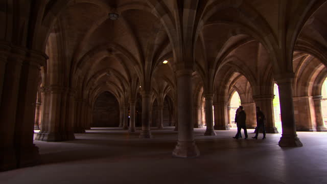 panning the vaulted arches and ceiling of a glasgow university walkway with some people walking and admiring the gothic architecture - art and craft stock videos & royalty-free footage