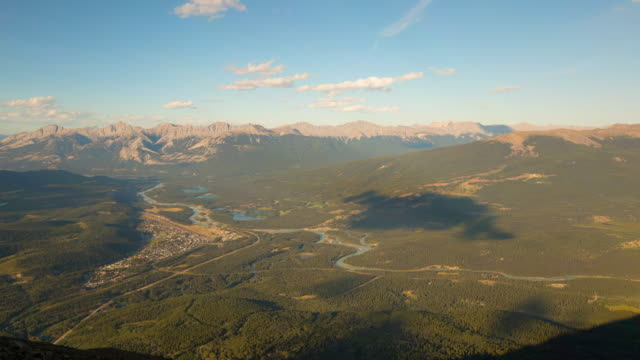 panning time lapse shot of city by river near mountains against sky on sunny day - jasper national park, canada - jasper national park stock videos & royalty-free footage