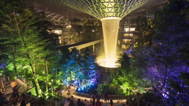 vídeos y material grabado en eventos de stock de 4k panning timelapse colorful wide angle view of giant waterfall in jewel, changi airport at night, singapore - natural landmark