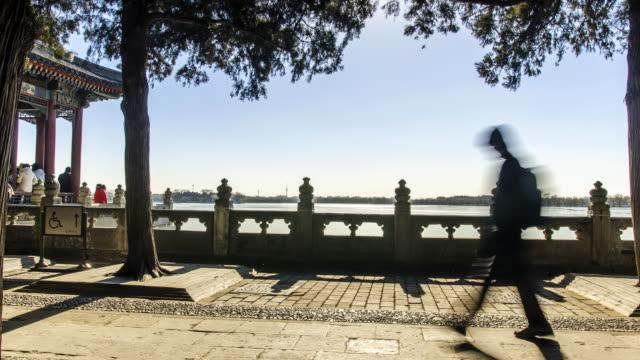 panning TL: Traveller walking under acrh tree at Bejing Summer palace