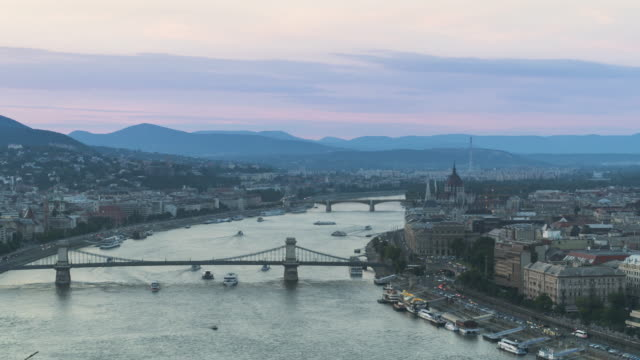 stockvideo's en b-roll-footage met pannen tl view: kettingbrug met stadsgezicht van boedapest rond de rivier de donau 's avonds vanaf gellért hill - chain bridge suspension bridge