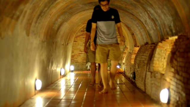panning : two persons walk out tunnel temple - temple body part stock videos and b-roll footage