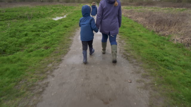 stockvideo's en b-roll-footage met a panning up shot of a mother and her two young sons walking through a muddy park - rubberlaars
