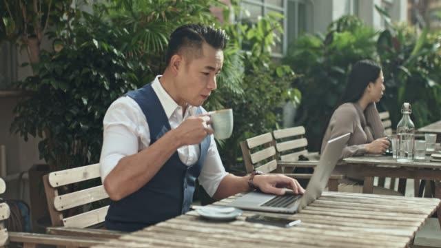 コーヒー カフェのテラスでノート パソコンでの作業で実業団のパンのビデオ