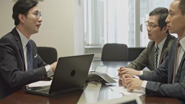 vidéos et rushes de panoramique vidéo d'hommes d'affaires chinois parler lors d'une réunion au bureau - recrue