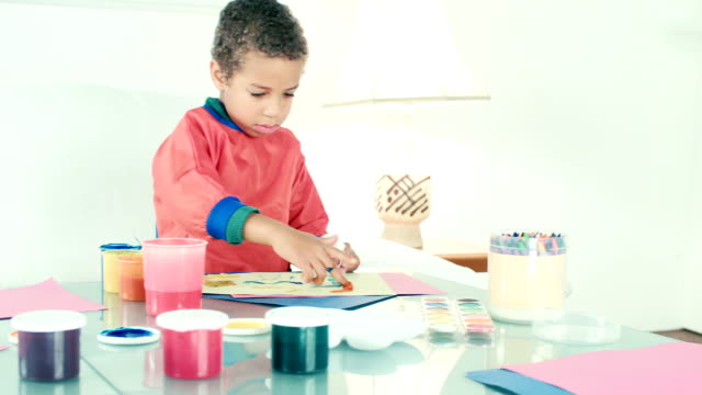 hd: panning video of little biracial boy finger painting - finger painting stock videos and b-roll footage