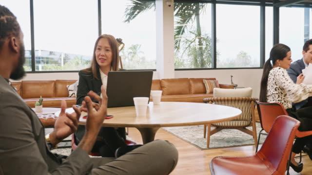 リラックスした環境で働く多民族ビジネスマンのパンニングビデオ - フリーアドレス点の映像素材/bロール
