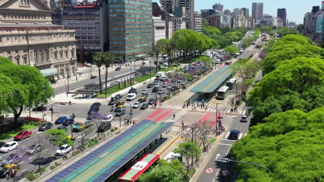 panning view. 9 de julio avenue, the widest road in the world, landmark in buenos aires. note solar panels on bus stops - avenida 9 de julio stock videos & royalty-free footage