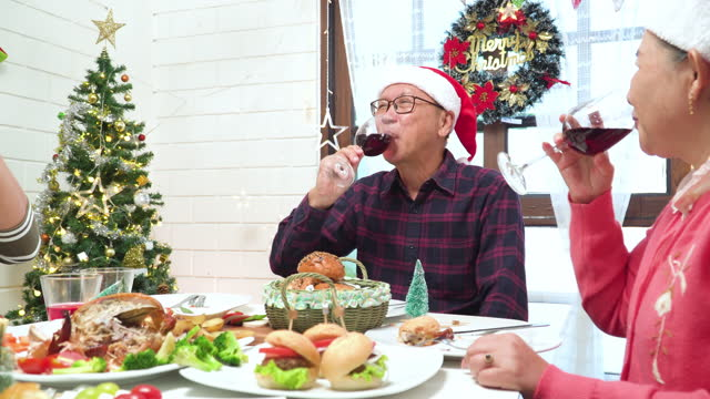 panning view: celebrate christmas with cheering with a drinking glass, red wine, orange juice together in southeast asian multi-generation family, grandfather, grandmother, father, mother, daughter, son in decorated home with tree and ornament. - 65 69 years stock videos & royalty-free footage