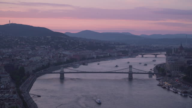 panning view:  chain bridge with cityscape of budapest around danube river at evening from gellért hill - ponte con catene ponte sospeso video stock e b–roll
