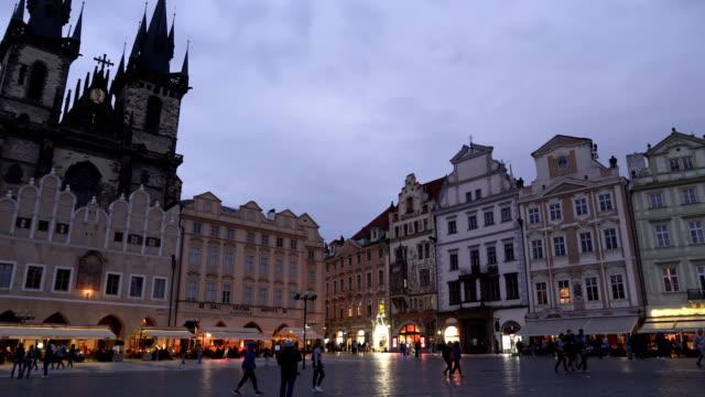 panning view: gothic styled building in old square containing crowd of traveller in prague at evening, czech republic - prague stock videos & royalty-free footage