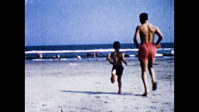 vidéos et rushes de panning view of beach full of people; boy in sailor suit; aerial view of beach parking lot; boy and man in swimwear running toward the ocean on the... - marin