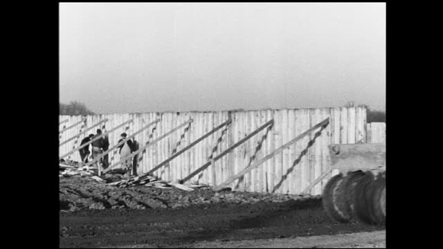 vídeos y material grabado en eventos de stock de panning view of construction site with foundation and building pillars visible; tractor drives across screen, fence held up by wooden planks in the... - 1940 1949