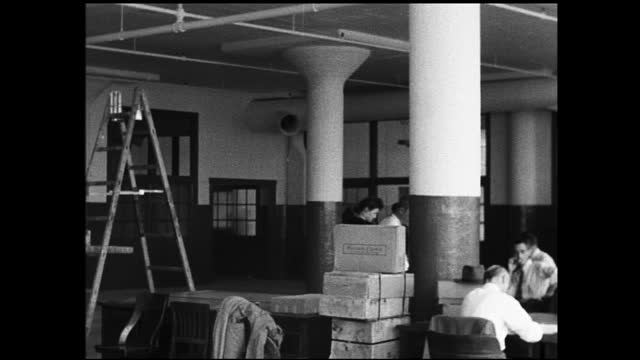 vídeos y material grabado en eventos de stock de panning view of construction workers painting wall and pipes; office staff work on the tables and talking to each other underneath - 1940 1949