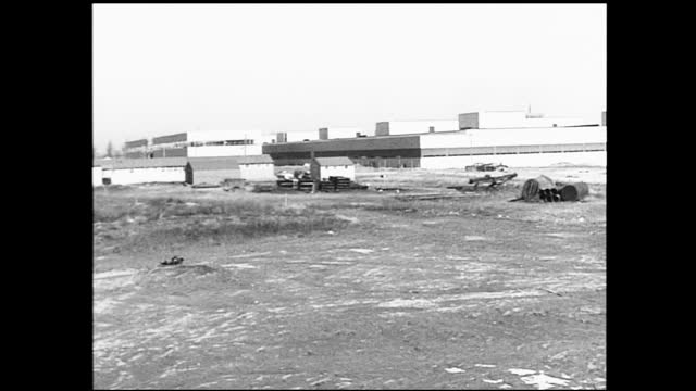 vídeos de stock e filmes b-roll de panning view of empty factory complex; car drives by in the distance; various ruins in the field - 1940 1949