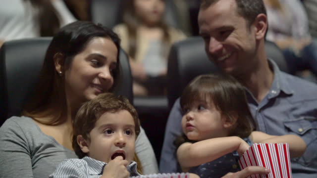panning view of family in the cinema watching a movie - film industry stock videos & royalty-free footage
