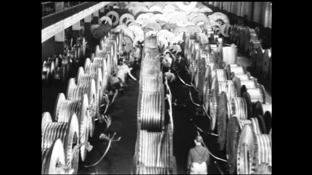panning view of interior of factory full of complex machinery; workers working on rows of large spools of cable; spools are lifted across the factory... - 1940 1949 stock videos & royalty-free footage