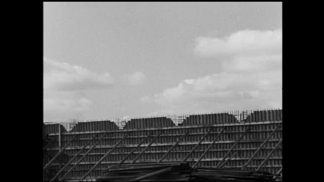 panning view of large building in construction and person walking by; large construction site with large crane and workers partially covered in snow;... - 1940 1949 video stock e b–roll